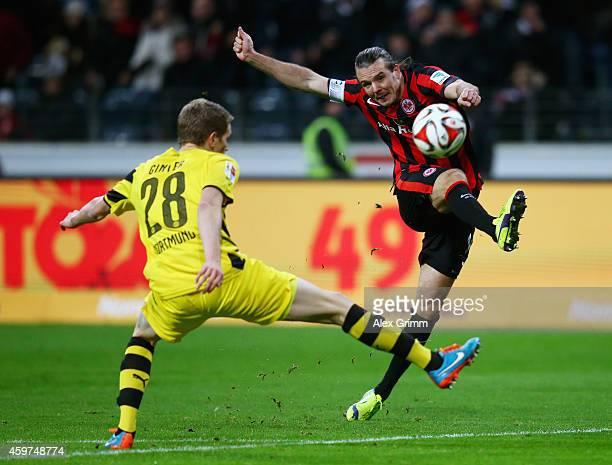 Alexander Meier of Eintracht Frankfurt takes a shot past Matthias Ginter of Borussia Dortmund during the Bundesliga match between Eintracht Frankfurt...