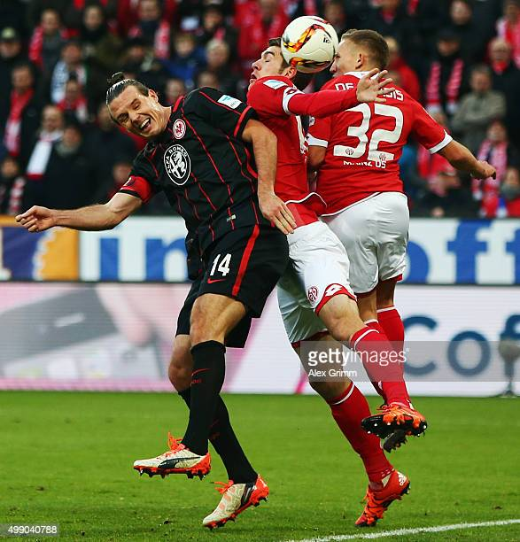 Alexander Meier of Frankfurt jumps for a header with Stefan Bell and Pablo de Blasis of Mainz during the Bundesliga match between 1 FSV Mainz 05 and...