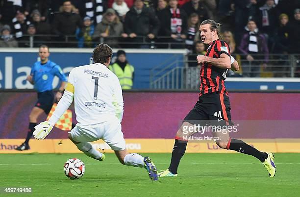 Alexander Meier of Frankfurt scores his team's first goal past goalkeeper Roman Weidenfeller of Dortmund during the Bundesliga match between...