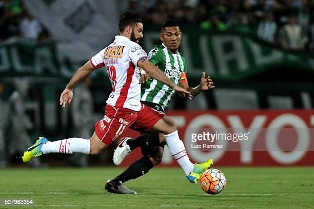 Alexander Mejia of Atletico Nacional vies for the ball with Jose San Roman of Huracan during a second leg match between Atletico Nacional and Huracan...