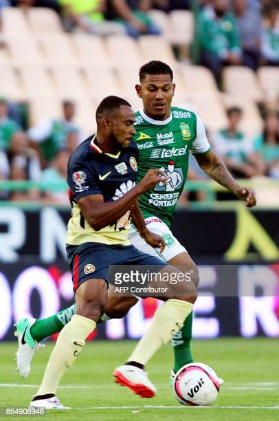 Alexander Mejia of Leon vies for the ball with William da Silva of America during their Mexican Apertura tournament football match at the Nou Camp...