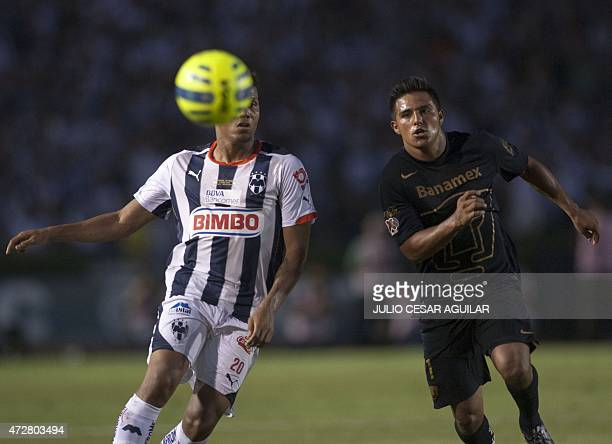 Alexander Mejia of Monterrey vie for the ball with Javier Cortes of Pumas during their 2015 Mexican Clausura tournament football match in Monterrey...