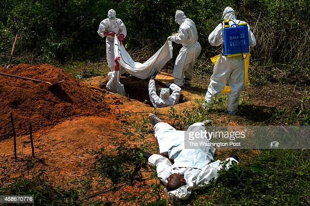 Alexander Morris lays flat on his back after fainted due to the extreme heat inside a protective suit while the Lofa County health department team...