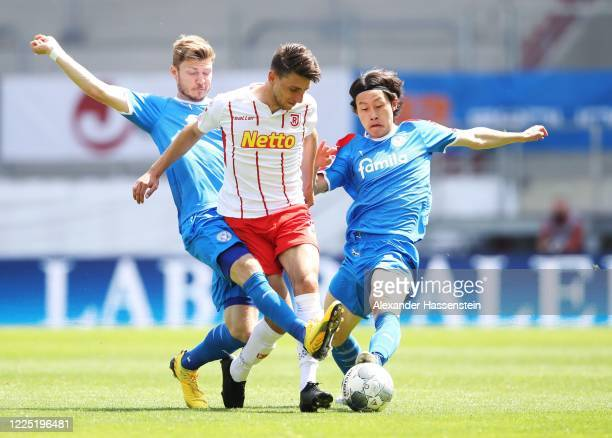 Alexander Muehling of Holstein Kiel and Lee Jae-Sung of Holstein Kiel challenge Charalampos Makridis of Jahn Regensburg during the Second Bundesliga...