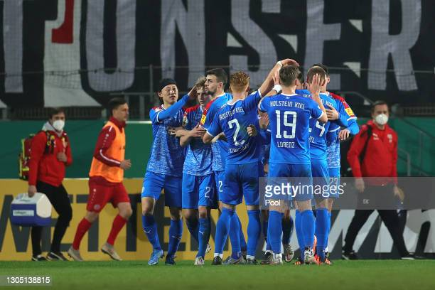 Alexander Muhling of Holstein Kiel celebrates with team mates after scoring their side's first goal from the penalty spot during the DFB Cup quarter...