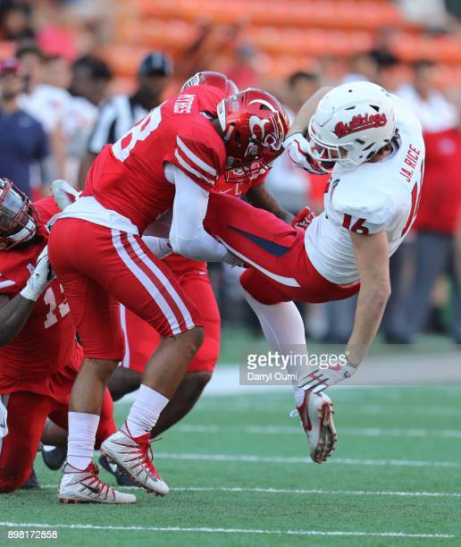 Alexander Myres of the Houston Cougars throws Jared Rice of the Fresno State Bulldogs to the ground during the second quarter of the Hawaii Bowl at...