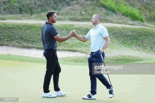 Alexander Noren of Sweden shakes hands with Brooks Koepka of the United States after defeating him 32 during the third round of the World Golf...