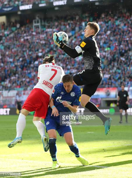 Alexander Nuebel of FC Schalke 04 catches the ball under pressure from Marcel Sabitzer of RB Leipzig during the Bundesliga match between RB Leipzig...