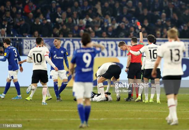 Alexander Nuebel of FC Schalke 04 is shown a red card by referee Felix Zwayer during the Bundesliga match between FC Schalke 04 and Eintracht...