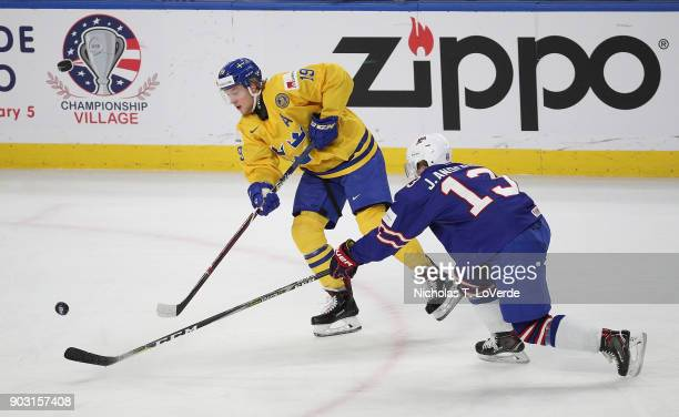 Alexander Nylander of Sweden passes the puck past Joey Anderson of United States during the second period of play in the IIHF World Junior...