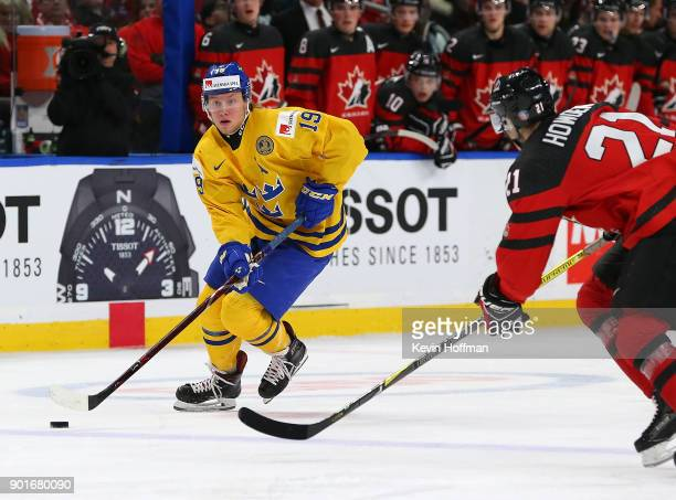 Alexander Nylander of Sweden skates up ice with the puck as Brett Howden of Canada defends in the second period during the Gold medal game of the...