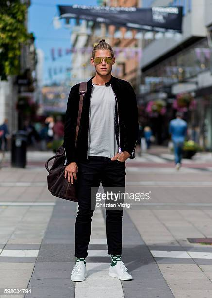 Alexander Olsson wearing a black jacket white tshirt weekender bag sunglasses and white sneaker during the second day of the Stockholm Fashion Week...