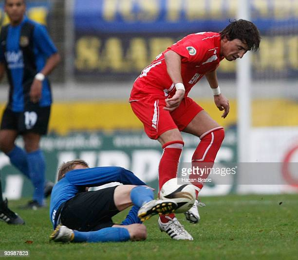 Alexander Otto of Saarbruecken battles for the ball with Dalibor Gataric of Worms during the Regionalliga match between 1 FC Saarbruecken and...