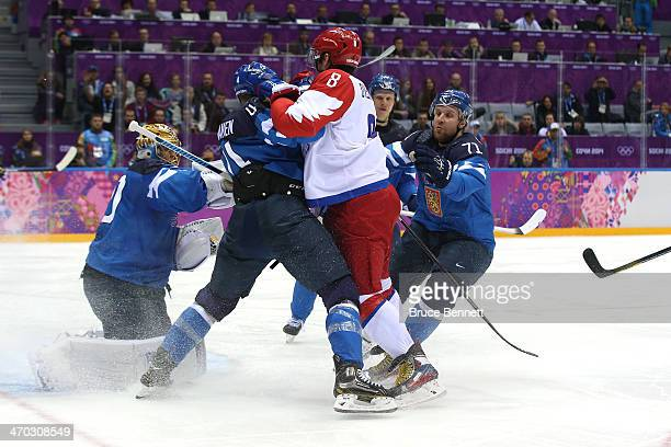 Alexander Ovechkin of Russia fights for position with Ossi Vaananen and Leo Komarov of Finland during the Men's Ice Hockey Quarterfinal Playoff on...