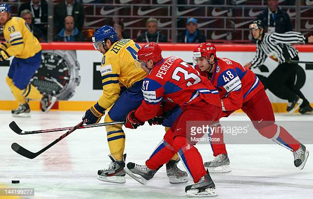 Alexander Perezhogin and Yevgeni Biryuko of Russia and Henrik Zetterberg of Sweden battle for the puck during the IIHF World Championship group S...