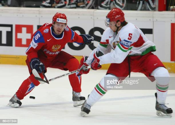 Alexander Perezhogin of Russia battles for the puck with Alexander Riadinski of Belarus during the IIHF World Championship Quarter-Final between...