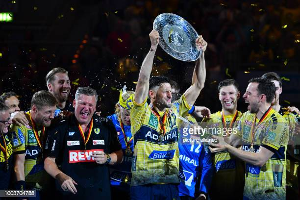 Alexander Petersson holds the championship shield and celebrates winning the German Championships with teammates after the German Bundesliga handball...
