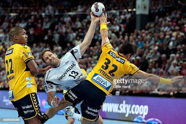 Alexander Petersson of Rhein Neckar challenges for the ball with Steffen Weinhold of Kiel during the DKB HBL Bundesliga match between THW Kiel and...