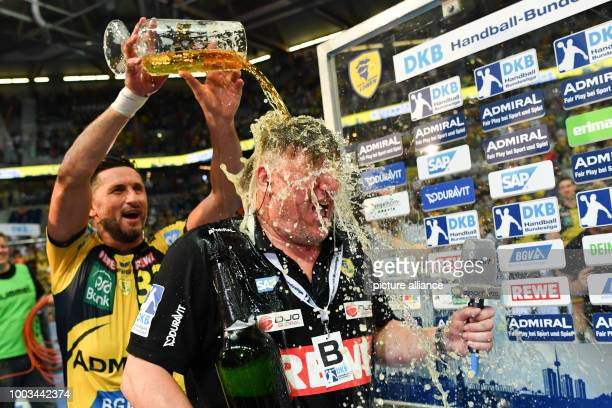 Alexander Petersson of RheinNeckar Loewen and coach Nikolaj Jacobsen celebrate winning the championships with a beer shower at the Bundesliga...