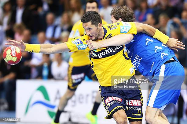 Alexander Petersson of RheinNeckar Loewen is challenged by Christoph Schindler of Gummersbach during the DKB Handball Bundesliga match between VfL...