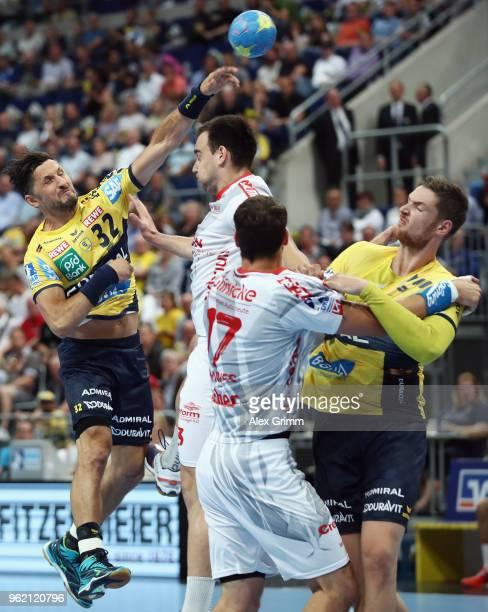 Alexander Petersson of RheinNeckar Loewen is challenged by Marino Maric and Felix Danner of Melsungen during the DKB HBL match between RheinNeckar...
