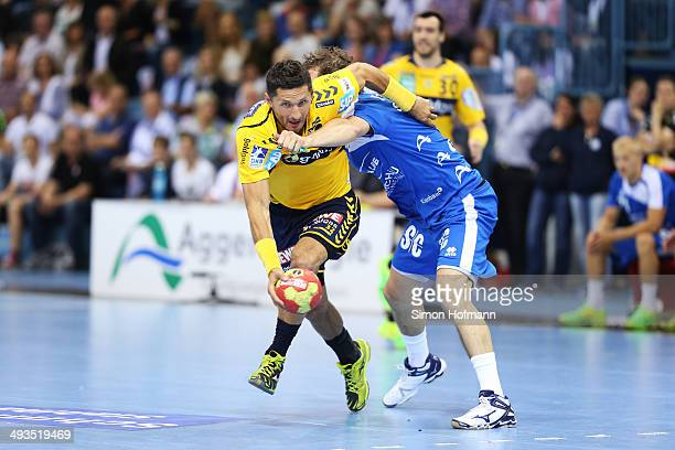 Alexander Petersson of RheinNeckar Loewen is challenged by Mark Bult of Gummersbach during the DKB Handball Bundesliga match between VfL Gummersbach...