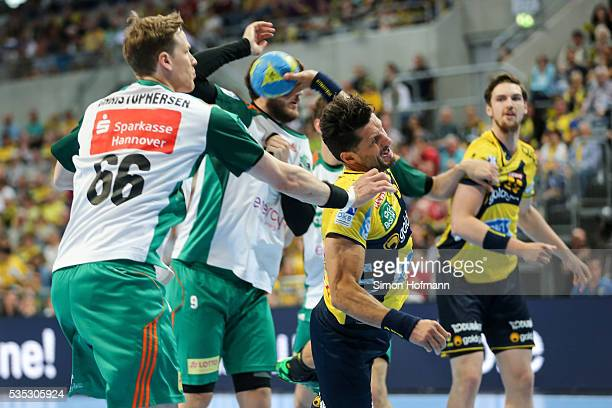 Alexander Petersson of RheinNeckar Loewen is challenged by SvenSoeren Christophersen of Hannover during the DKB Handball Bundesliga match between...