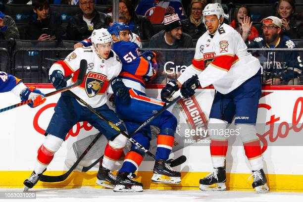 Alexander Petrovic and Juho Lammikko of the Florida Panthers check Valtteri Filppula of the New York Islanders into the boards at Barclays Center on...