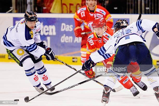 Alexander Preibisch of DEG is challenged by Rene Roethke and Rene Kramer of Straubing Tigers during the DEL Ice Hockey match between Duesseldorfer EG...