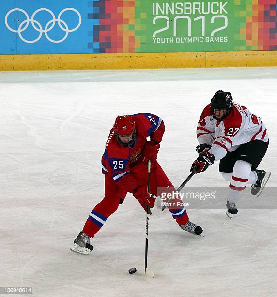 Alexander Protapovich of Russia and Joseph Hicketts of Canada battle for the puck during the men's preliminary round ice hockey match between Russia...