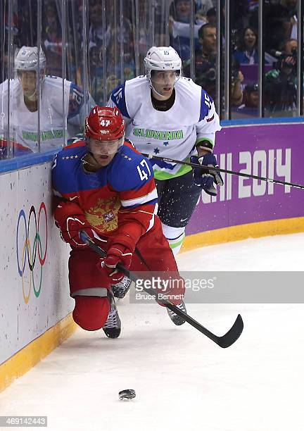 Alexander Radulov of Russia handles the puck against Blaz Gregorc of Slovenia in the first period during the Men's Ice Hockey Preliminary Round Group...