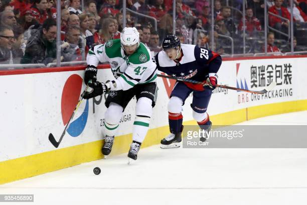 Alexander Radulov of the Dallas Stars and Christian Djoos of the Washington Capitals skate after the puck at Capital One Arena on March 20 2018 in...