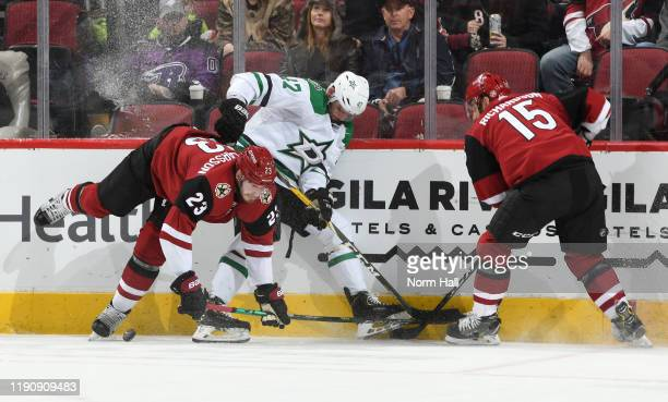 Alexander Radulov of the Dallas Stars battles for the puck along the boards with Oliver Ekman-Larsson and Brad Richardson of the Arizona Coyotes...