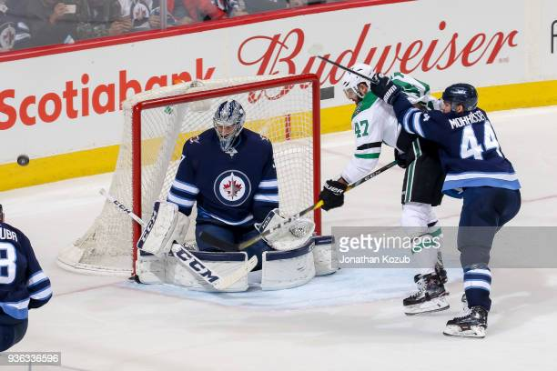 Alexander Radulov of the Dallas Stars battles with Josh Morrissey of the Winnipeg Jets in front of goaltender Connor Hellebuyck as the puck flies by...