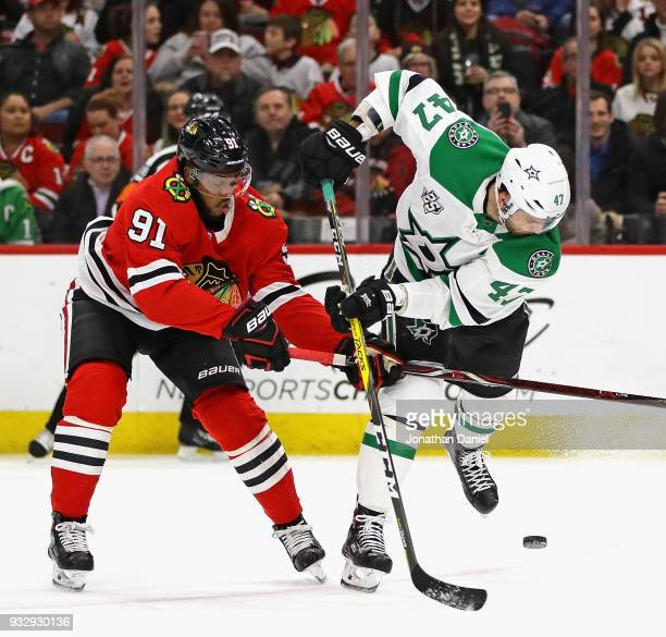 Alexander Radulov of the Dallas Stars tries to control the puck under presure from Anthony Duclair of the Chicago Blackhawks at the United Center on...