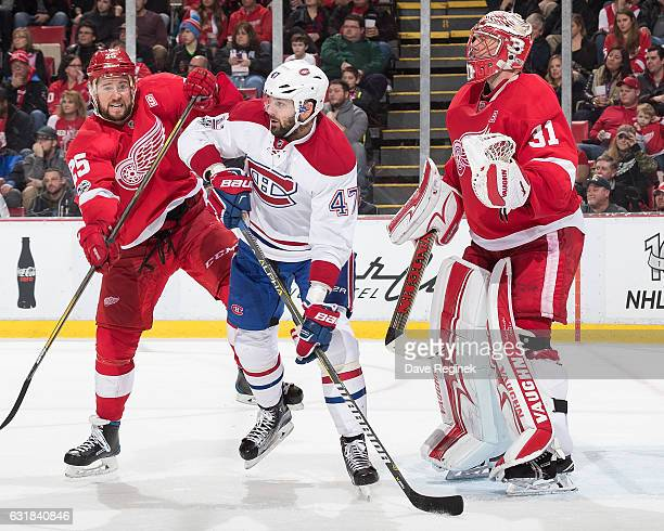 Alexander Radulov of the Montreal Canadiens battles for position with Mike Green of the Detroit Red Wings in front of Jared Coreau of the Wings...
