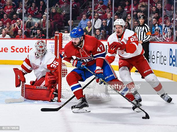 Alexander Radulov of the Montreal Canadiens skates the puck against Danny DeKeyser of the Detroit Red Wings near goaltender Jimmy Howard during the...