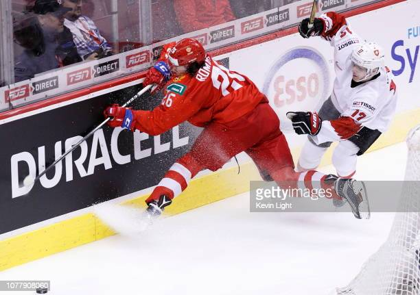 Alexander Romanov of Russia crashes into the boards while being chased by Luca Wyss of Switzerland during a bronze medal game at the IIHF World...