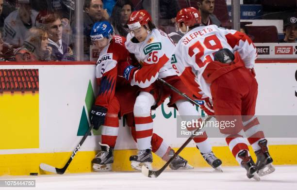 Alexander Romanov of Russia hits Matej Pekar of the Czech Republic along the side boards as Kirill Slepets of Russia looks on in Group A hockey...