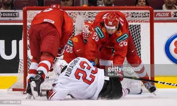 Alexander Romanov of Russia knocks down Philipp Kurashev of Switzerland in front of the net in Bronze Medal hockey action of the 2019 IIHF World...