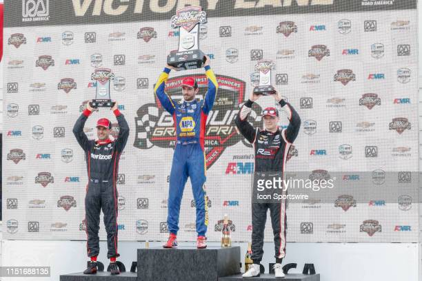 Alexander Rossi Andretti Autosport Honda celebrates winning the NTT IndyCar Series REV Group Grand Prix with Team Penske Chevy drivers Will Power and...