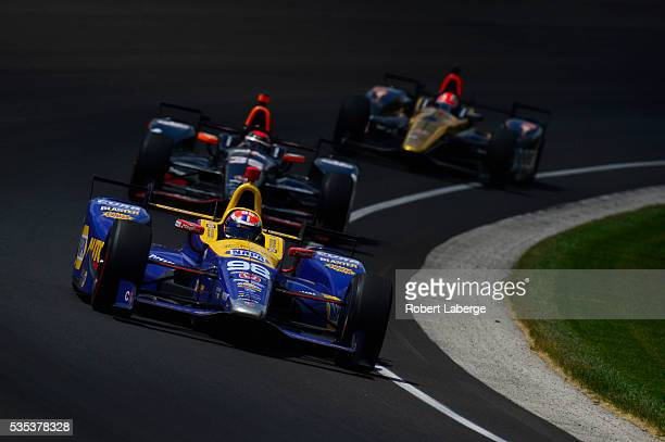 Alexander Rossi driver of the Andretti Herta Autosport Dallara Honda leads a pack of cars on his way to winning the 100th running of the Indianapolis...