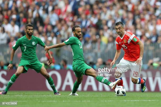 Alexander Samedov of Russia runs with the ball past a challenge from Abdullah Otayf of Saudi Arabia during the 2018 FIFA World Cup Russia Group A...
