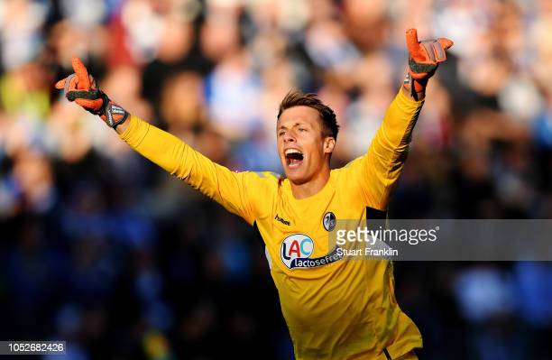 Alexander Schwolow of Freiburg celebrates as Robin Koch of Freiburg scores his team's first goal during the Bundesliga match between Hertha BSC and...
