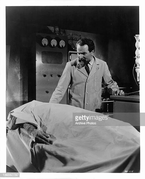 Alexander Scourby looking down at covered cadaver in a scene from The Deadly Games Affair episode from the television series 'The Man From UNCLE' 1964