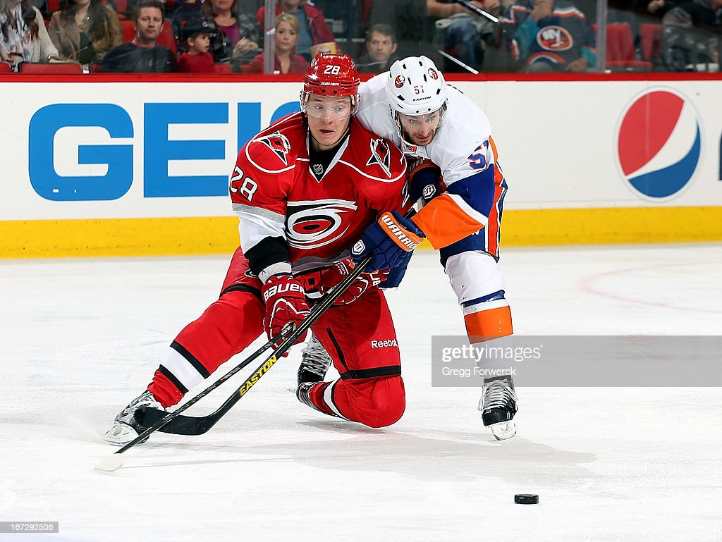 Alexander Semin #28 of the Carolina Hurricanes and Frans Nielsen #51 of the New York Islanders battle to get to the puck during their NHL game at PNC Arena on April 23, 2013 in Raleigh, North Carolina.