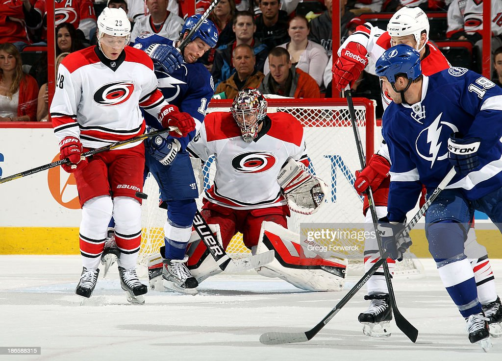 Alexander Semin #28 of the Carolina Hurricanes and Ryan Malone #12 of the Tampa Bay Lightning react to a shot as Justin Peters #35 prepares to make a save during an NHL game at PNC Arena on November1, 2013 in Raleigh, North Carolina.