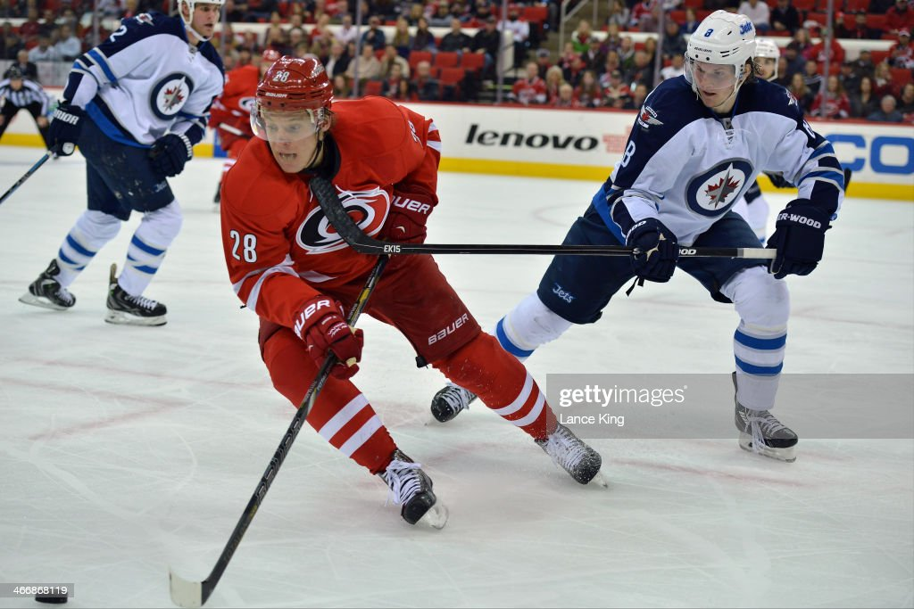 Alexander Semin #28 of the Carolina Hurricanes controls the puck against Jacob Trouba #8 of the Winnipeg Jets at PNC Arena on February 4, 2013 in Raleigh, North Carolina. The Jets defeated the Hurricanes 2-1.