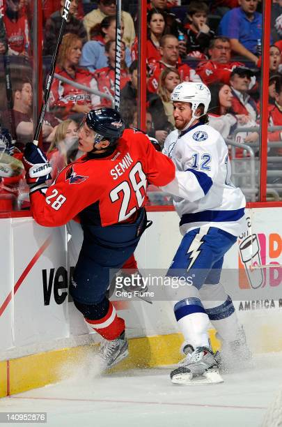 Alexander Semin of the Washington Capitals is checked into the boards by Ryan Malone of the Tampa Bay Lightning at the Verizon Center on March 8 2012...