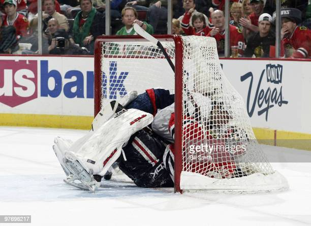 Alexander Semin of the Washington Capitals lands in the net with goalie Antti Niemi of the Chicago Blackhawks on March 14 2010 at the United Center...